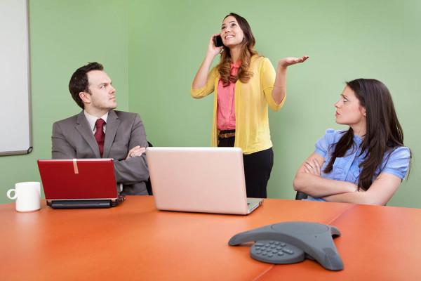 Rude colleague disturbing meeting by talking on Smartphone